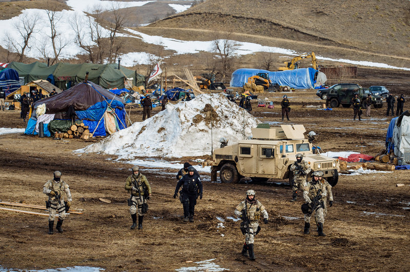 Police move through the camp of protesters against the Dakota Access Pipeline near Cannon Ball, N.D.jpg